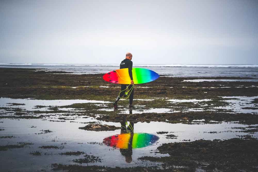 man in black wetsuit carrying red, yellow, blue, and green surfboard