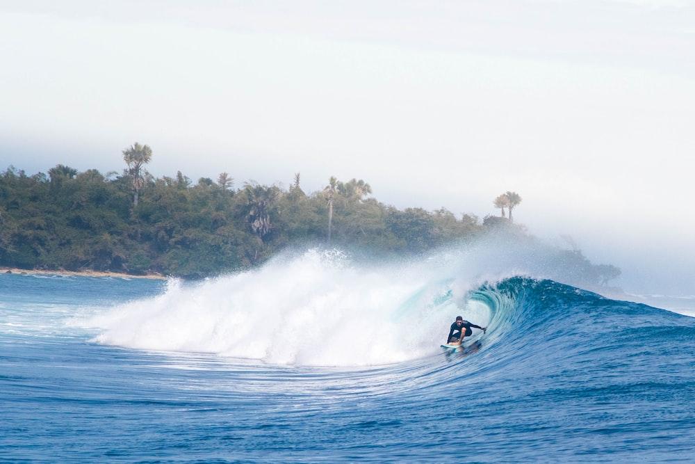 man surfing on big waves under white sky