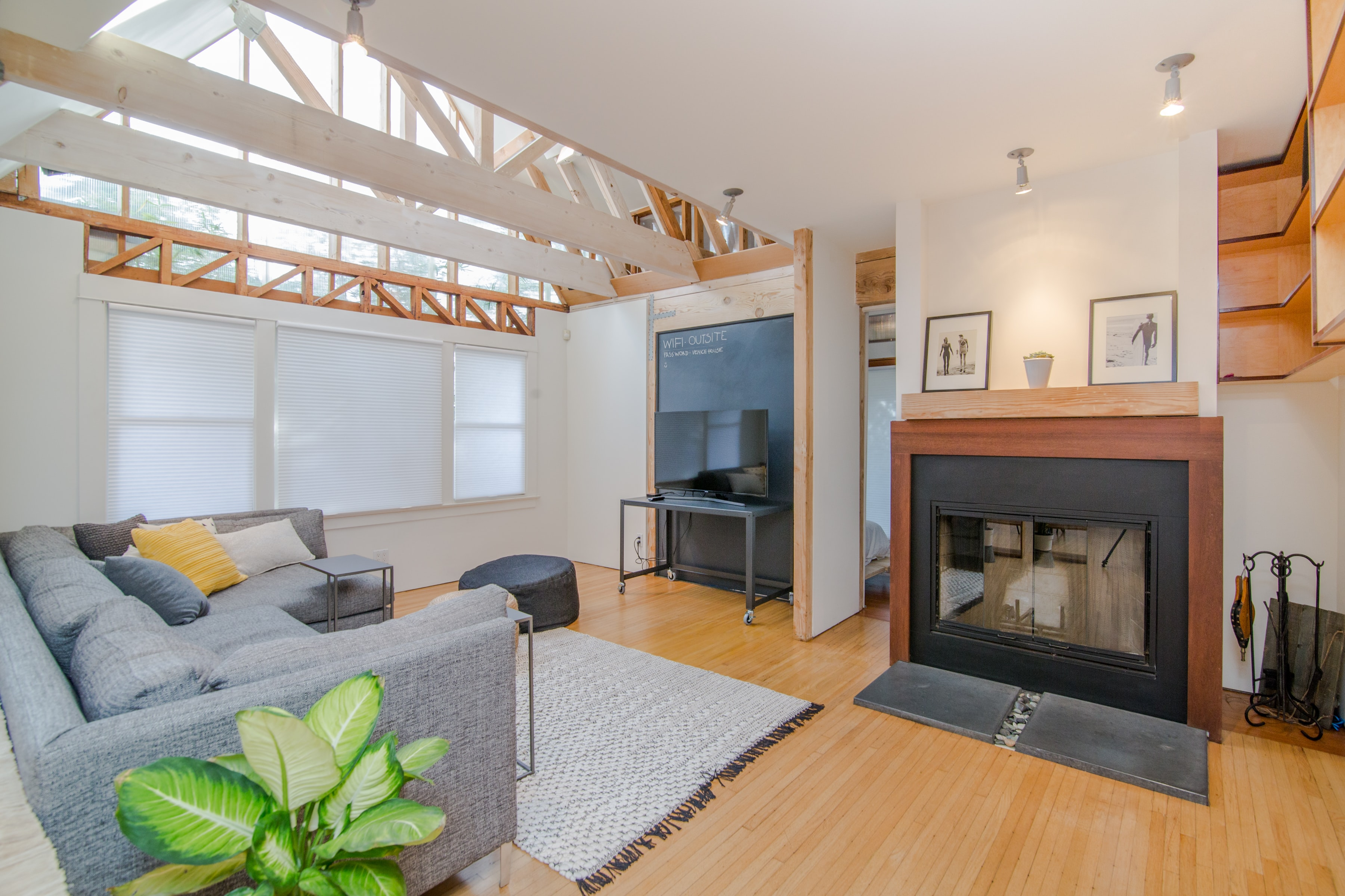 Bright living room with beams on the ceiling, a rug, plant, and fireplace