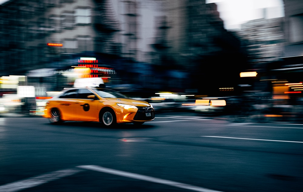 orange coupe running on gray street during daytiem