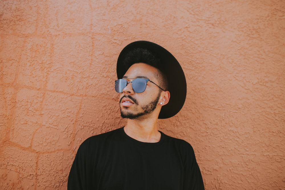 man leaning on brown wall