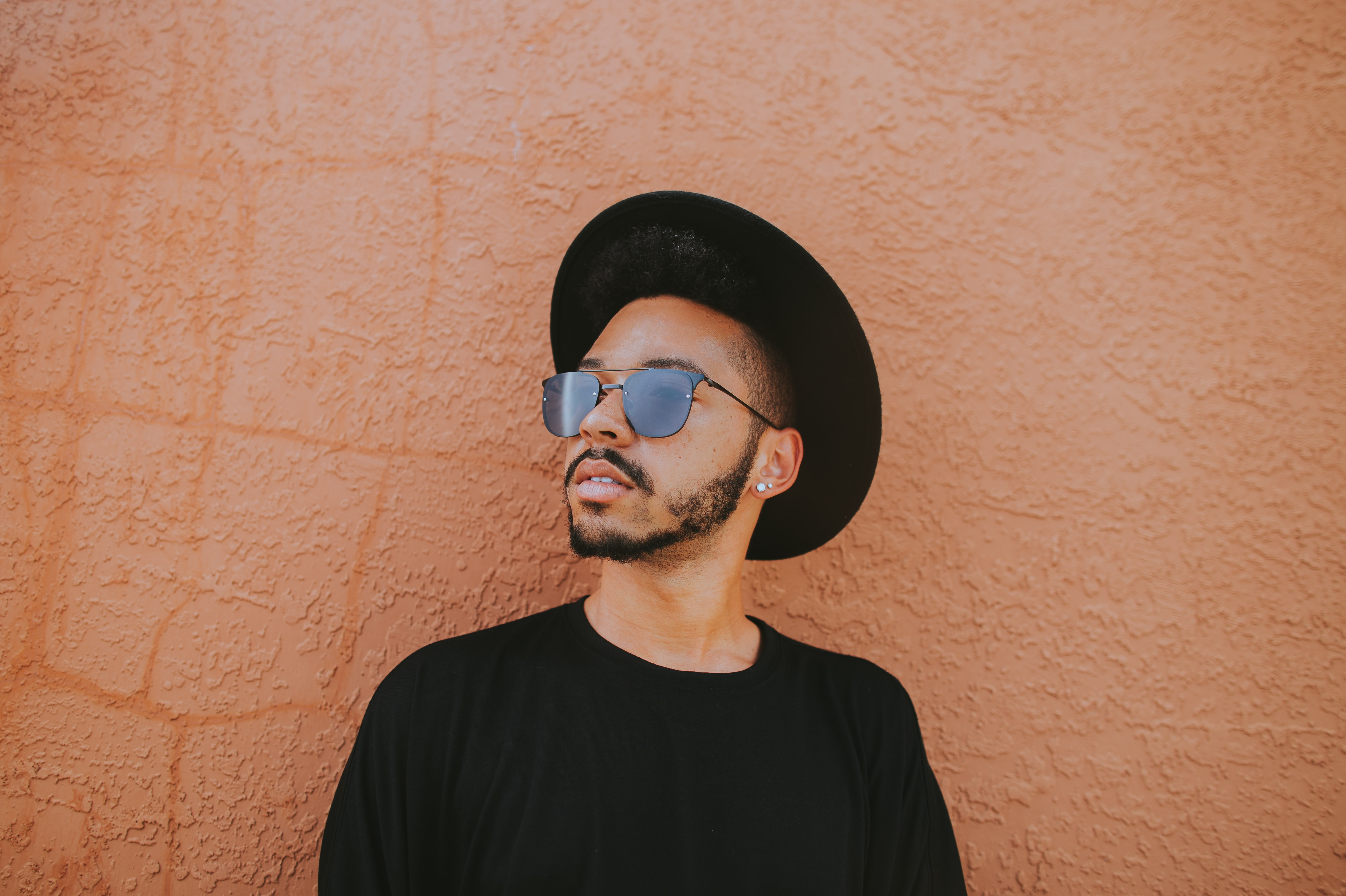 A man in a black hat and sunglasses standing next to an orange wall