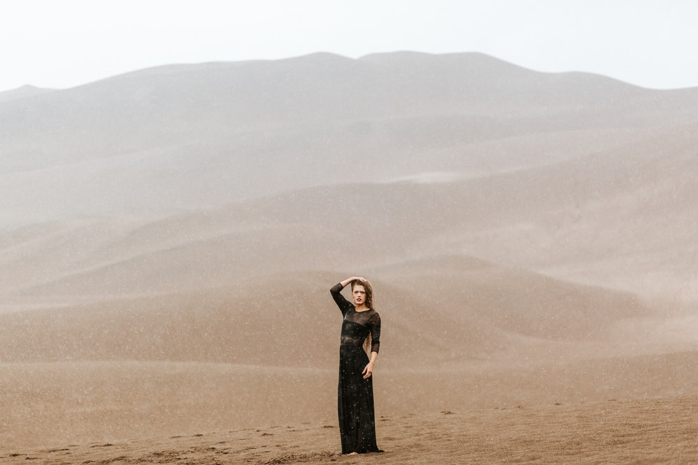 woman standing on brown sands