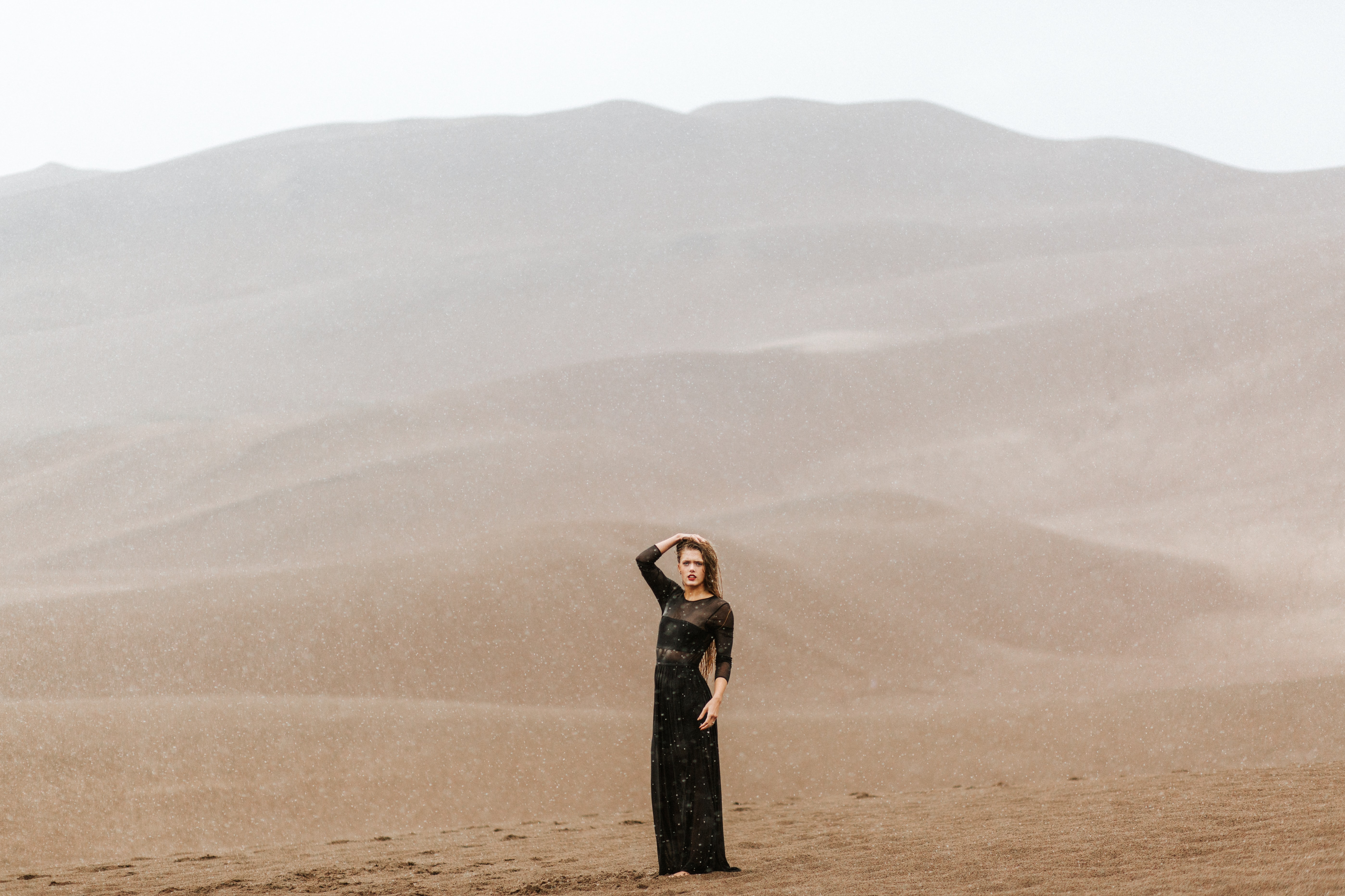 Fashionable woman models in desolate sandy desert