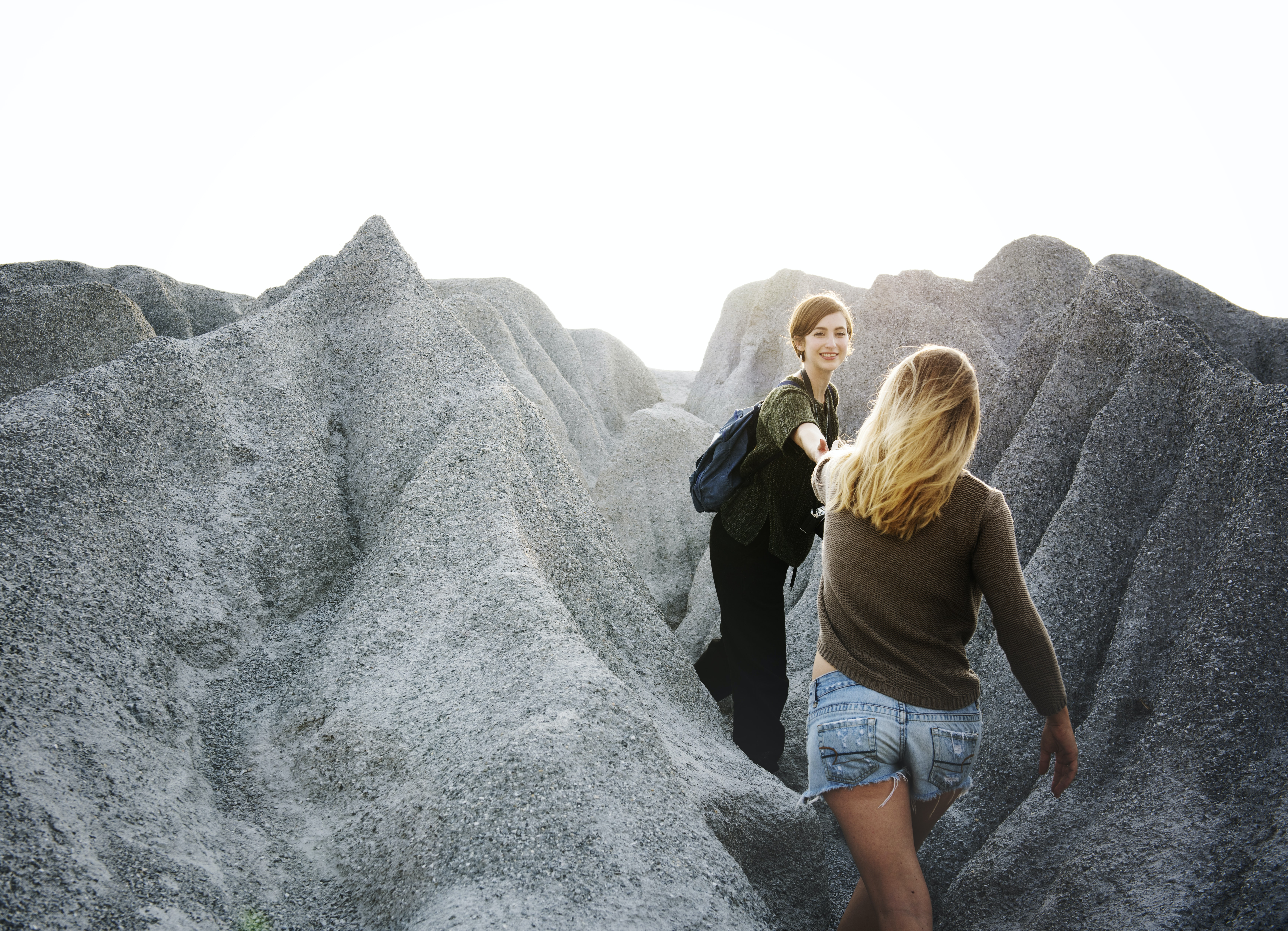 woman holding hand of another woman between rock cliff