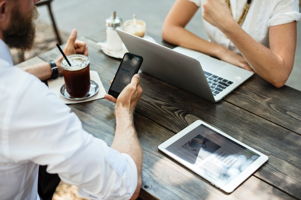 Two business people sitting at a coffee shop table with a laptop, a tablet and a smartphone