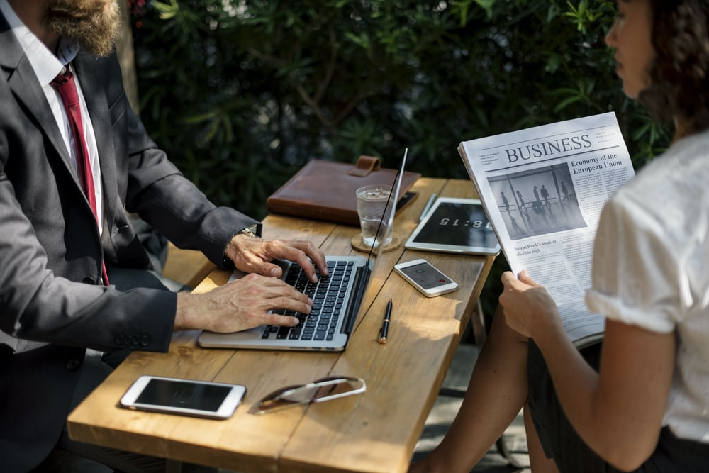 Two businesspeople with a newspaper and a laptop at an outdoor table