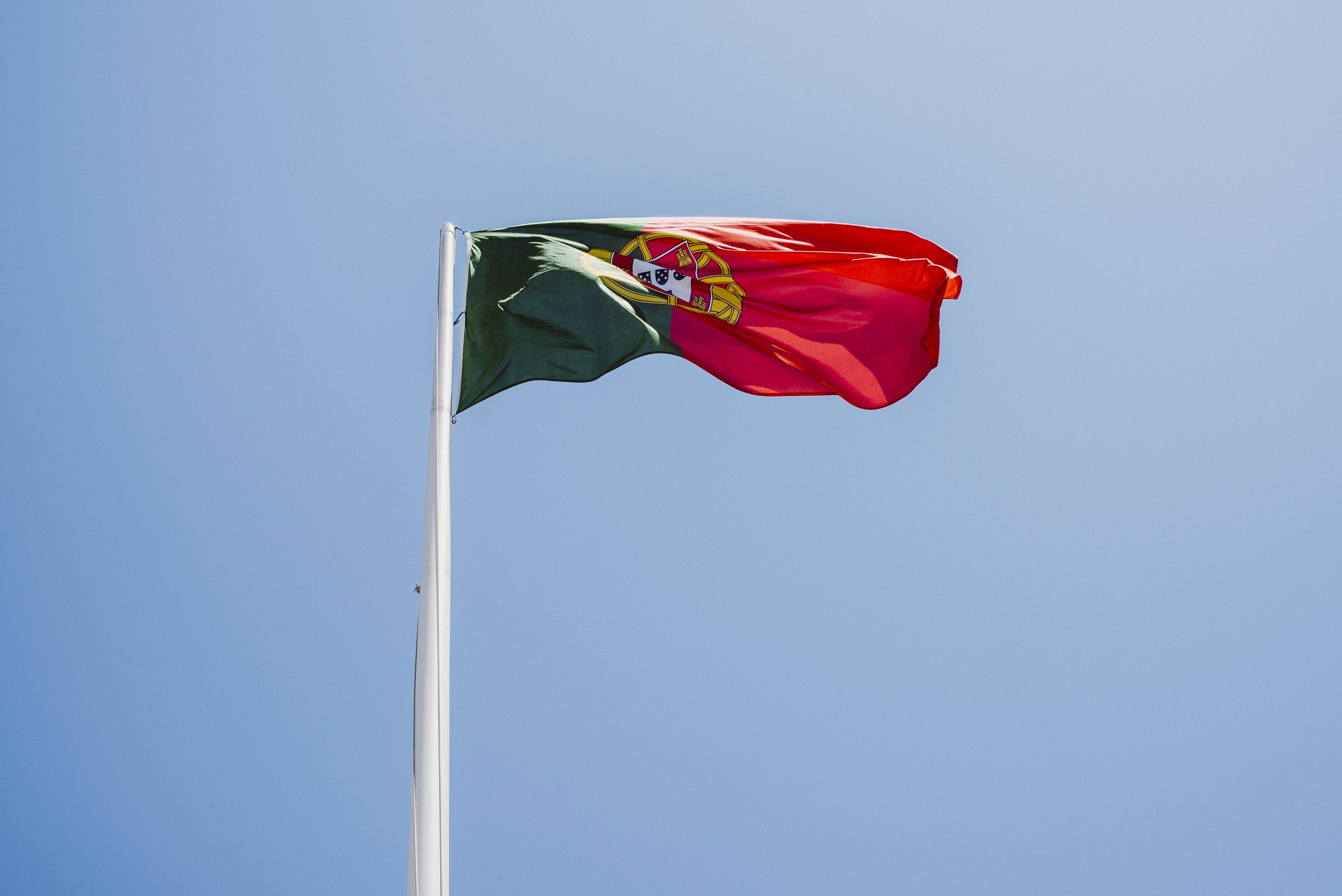 flag of Portugal hoisted on white metal pole