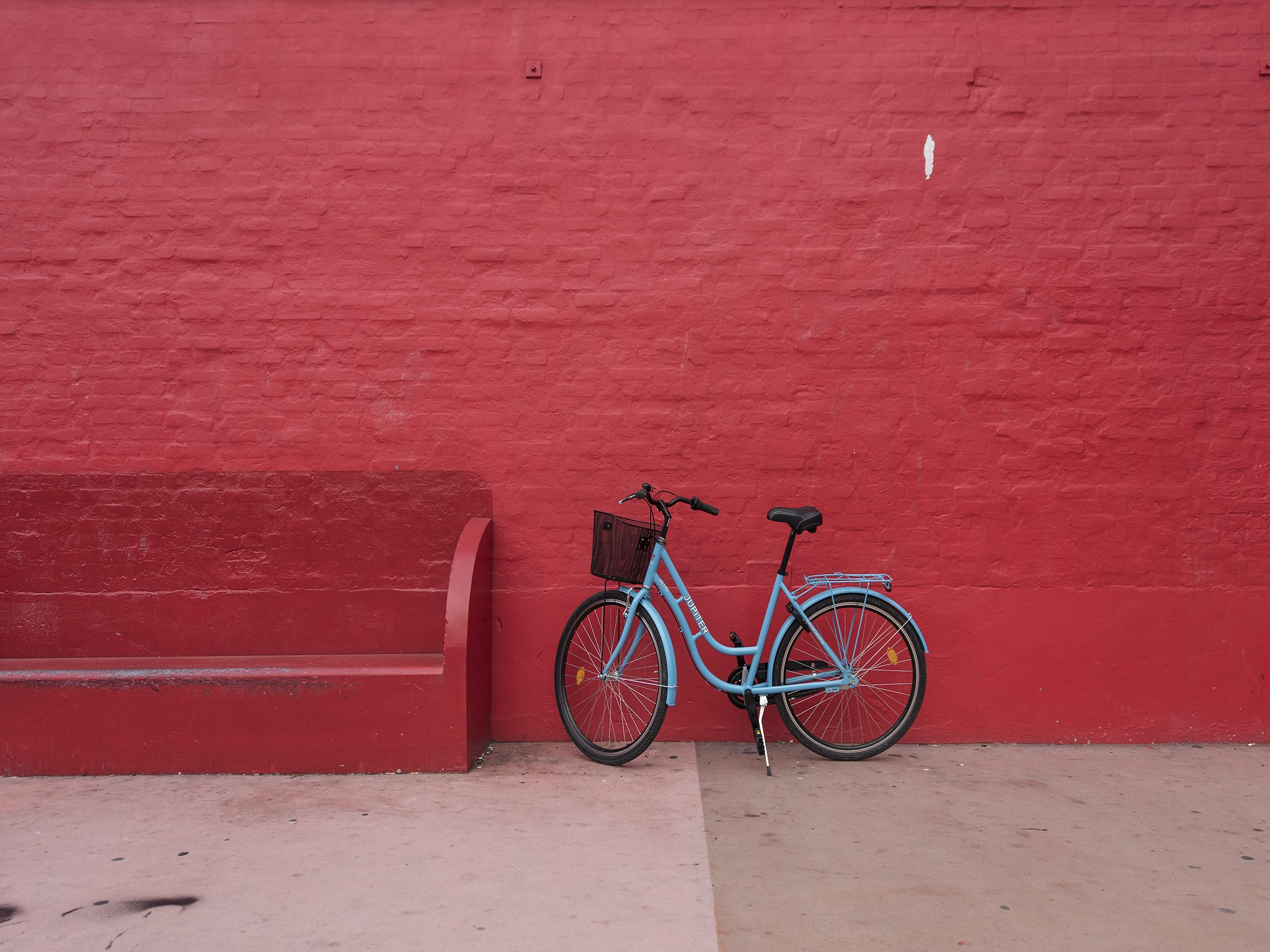 blue step-through bicycle park beside of red bench