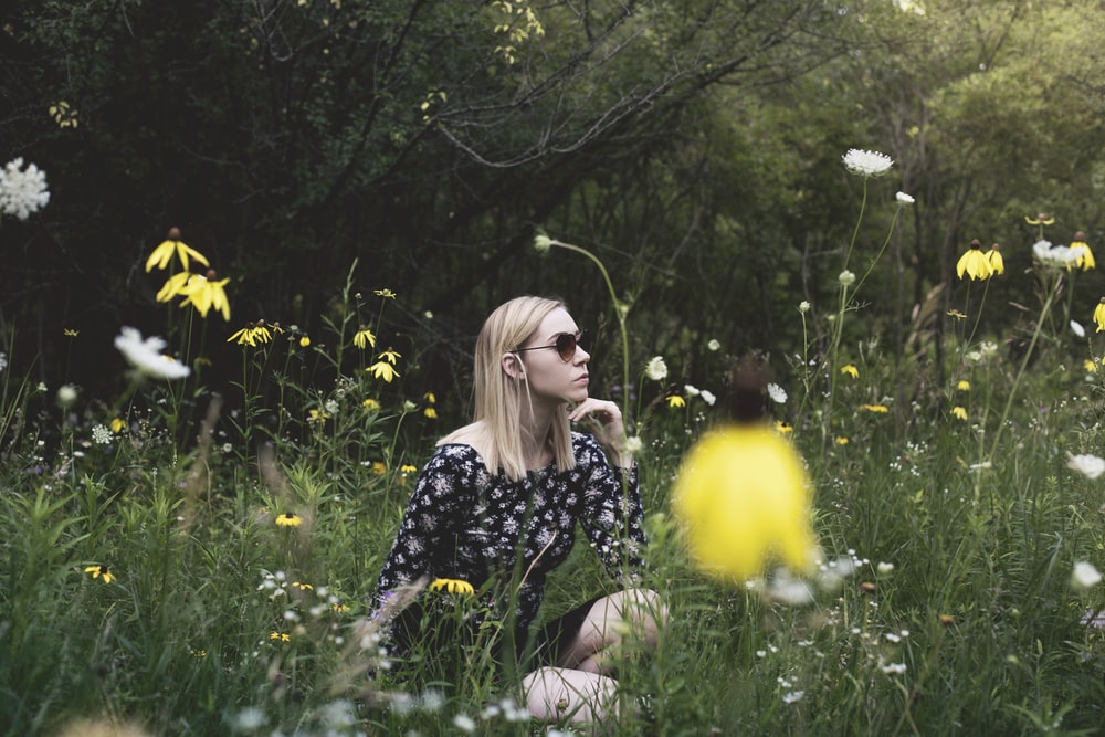 woman sitting on grass field surrounded with flowers while hand on chin