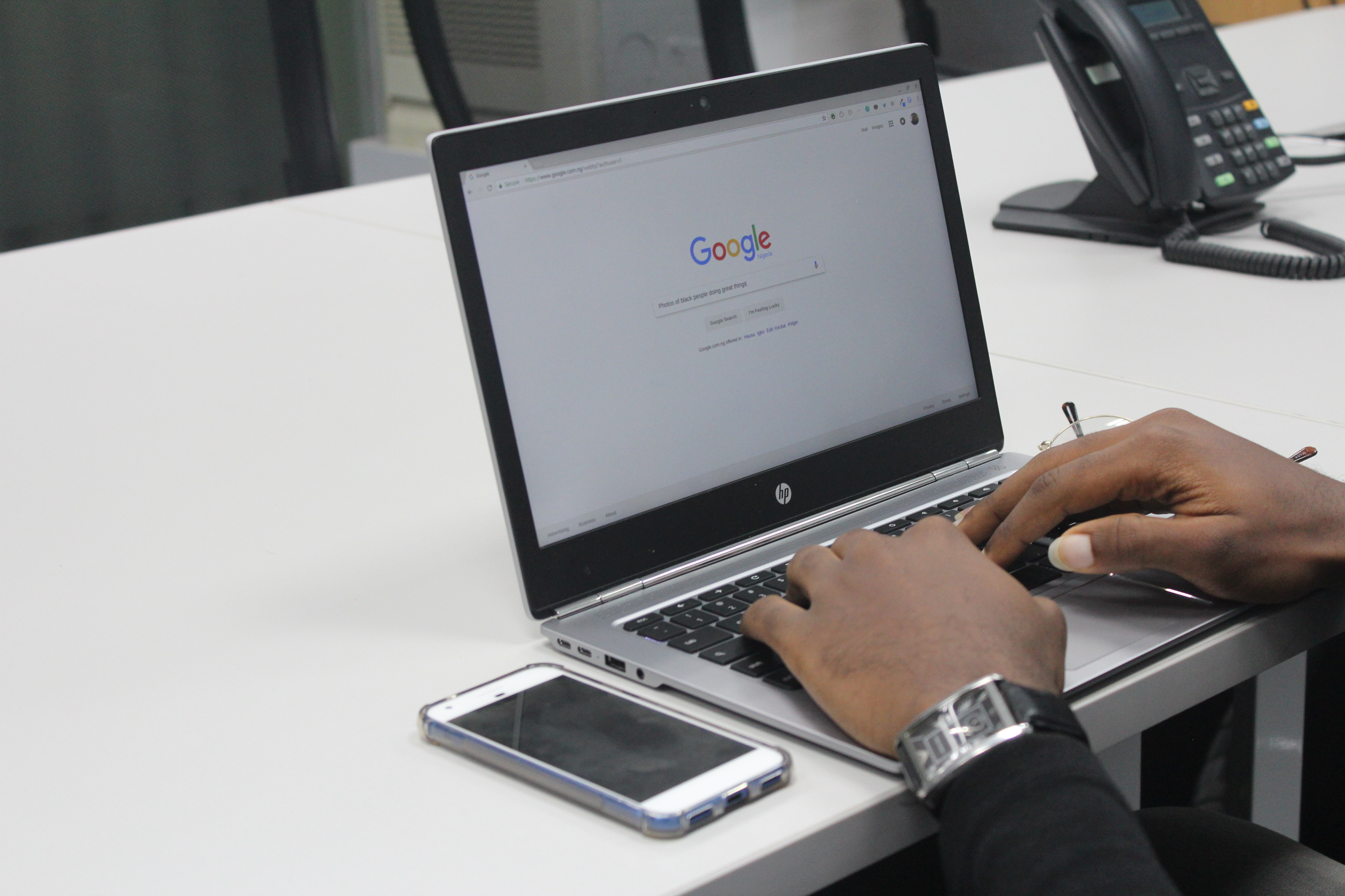 Person with watch using laptop computer and Google search engine with iPhone on table