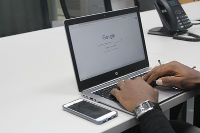 person typing on gray and black hp laptop google teams background