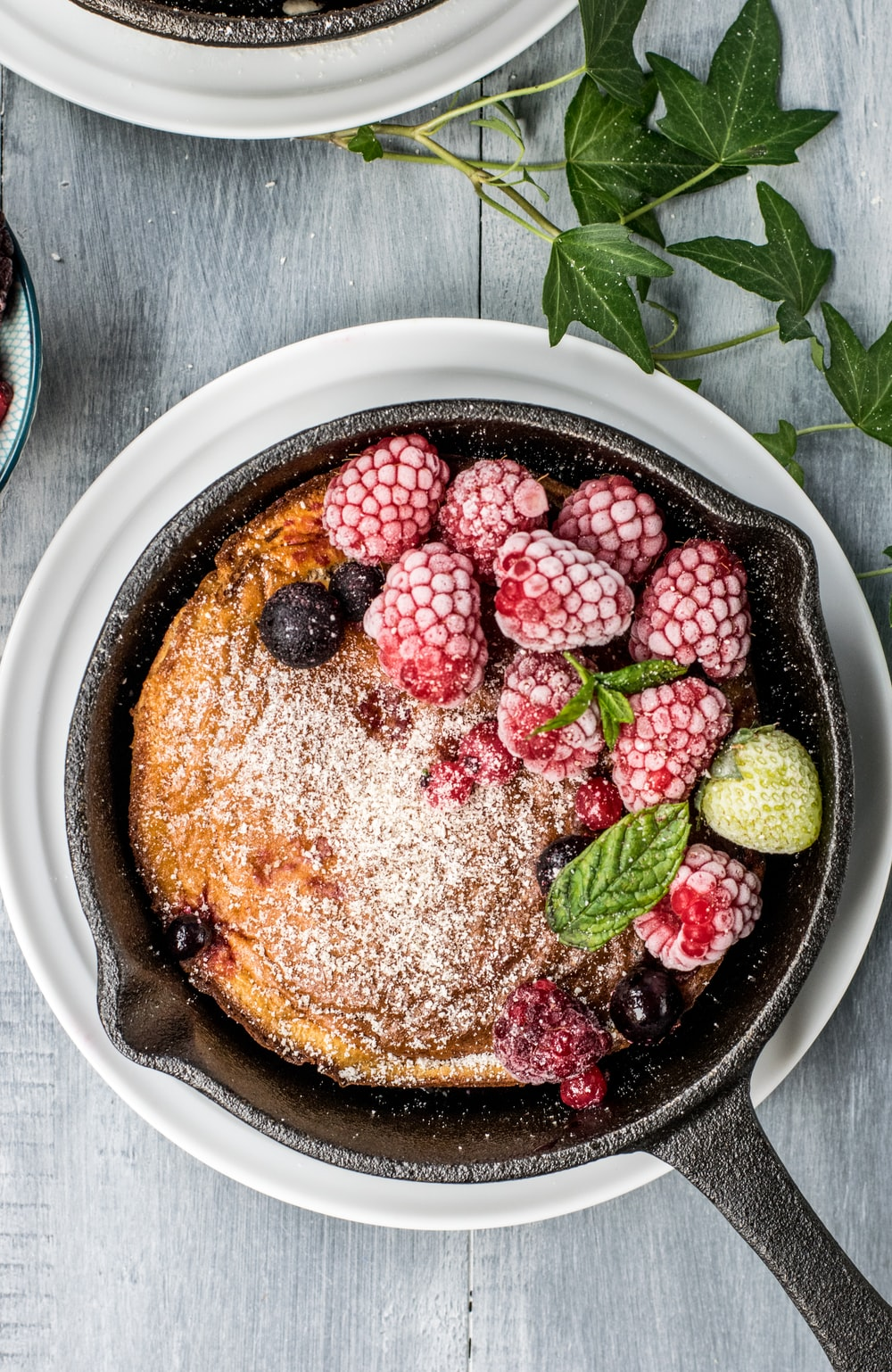 pancake with raspberry and blueberries on black cast-iron skillet