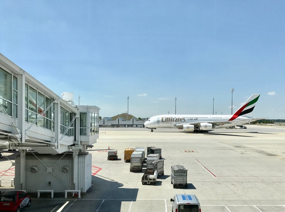 white Emirates airplane on airport
