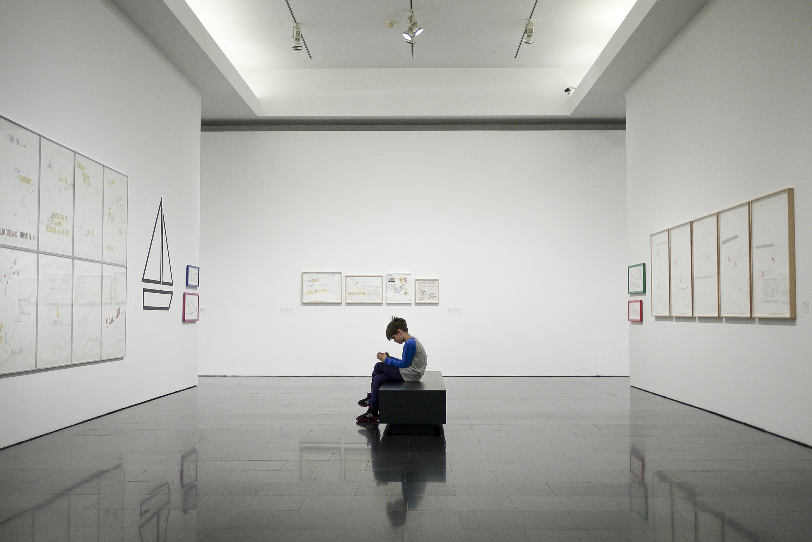 Boy sitting alone inside large gallery room with white walls viewing exhibition in Barcelona