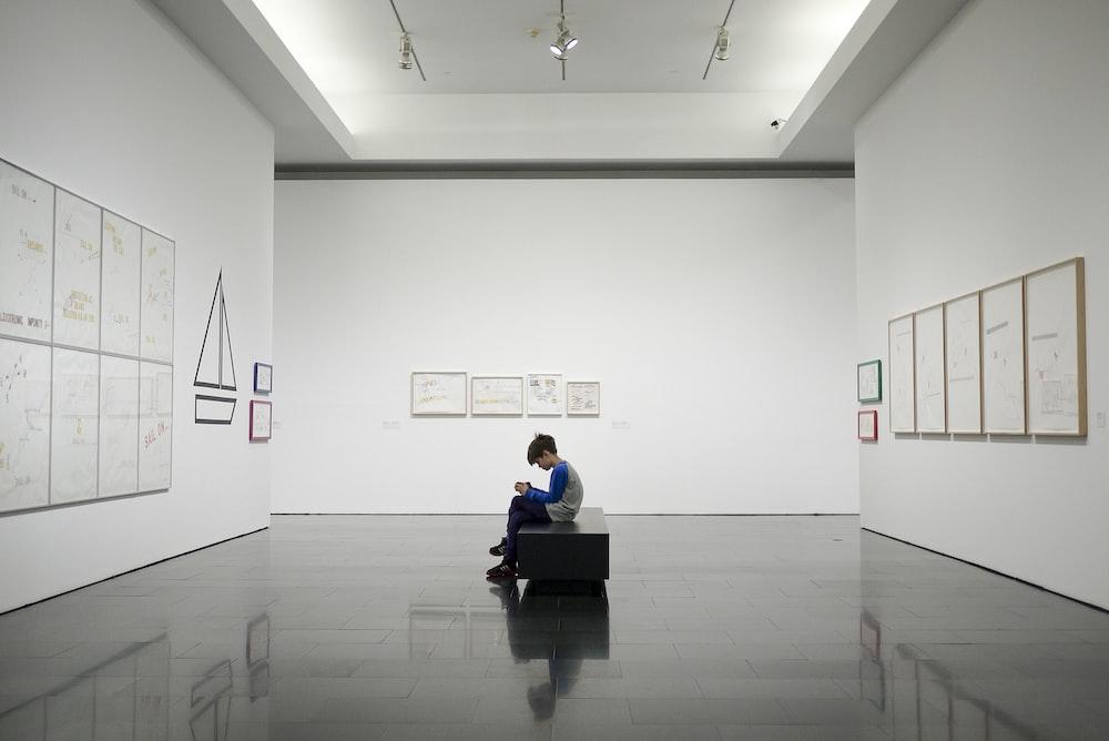 man sitting near museum painting