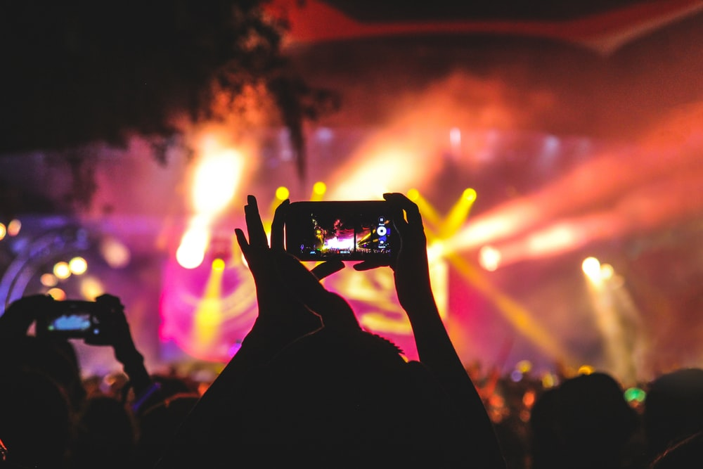 person holding smartphone taking video of a concert near stage with lights during nighttime