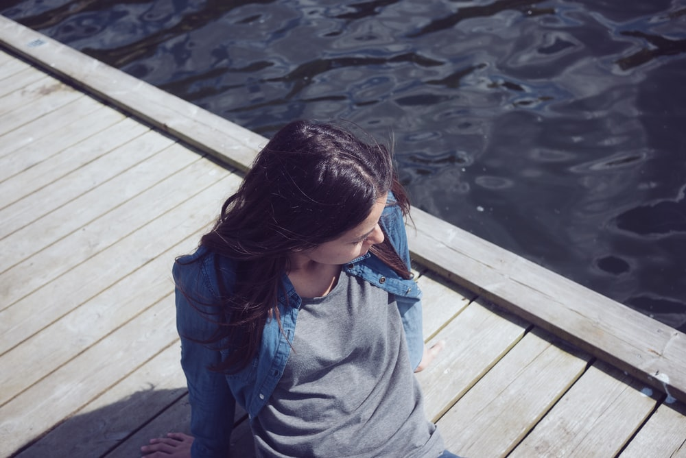 woman in grey top seating on dock during daytime