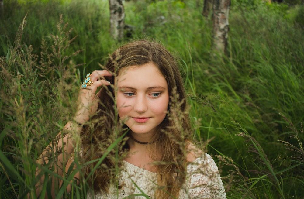 woman brushing her hair inside tall grass field