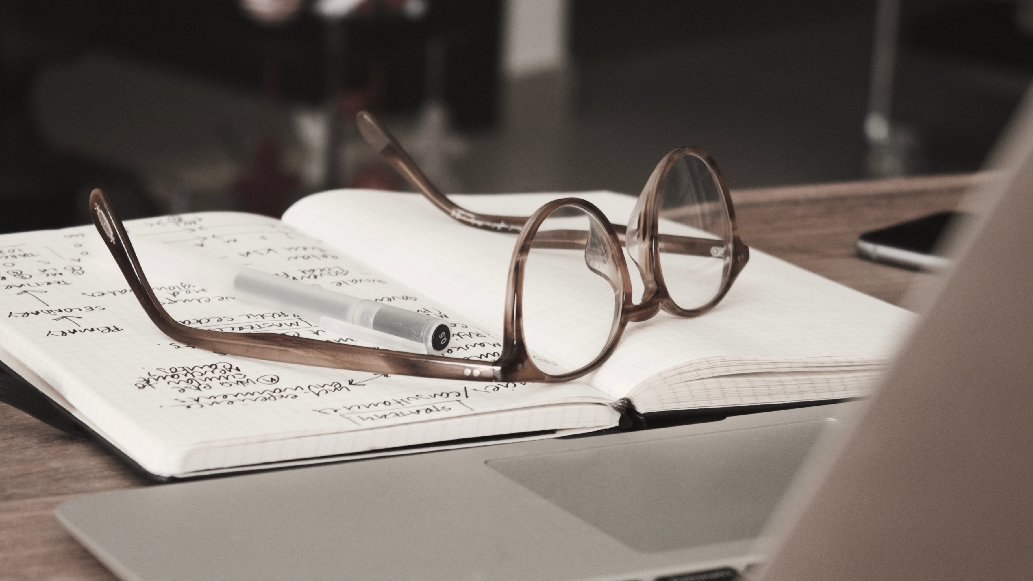eyeglasses with gray frames on the top of notebook