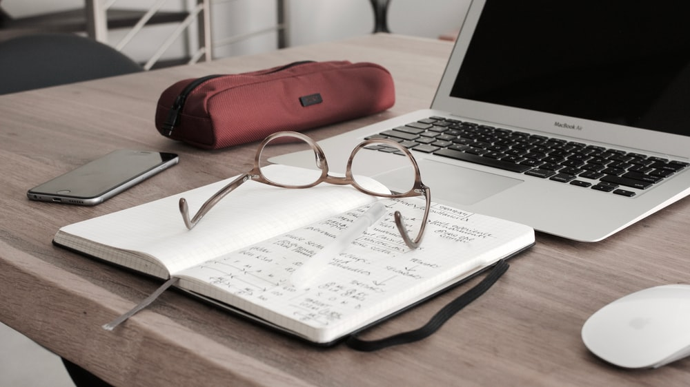 Laptop and notebook with glasses on top of a wooden desk