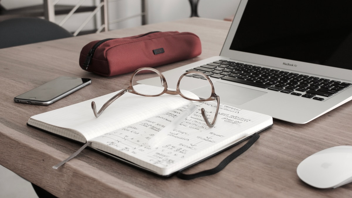 eyeglasses on a notebook in front of a laptop