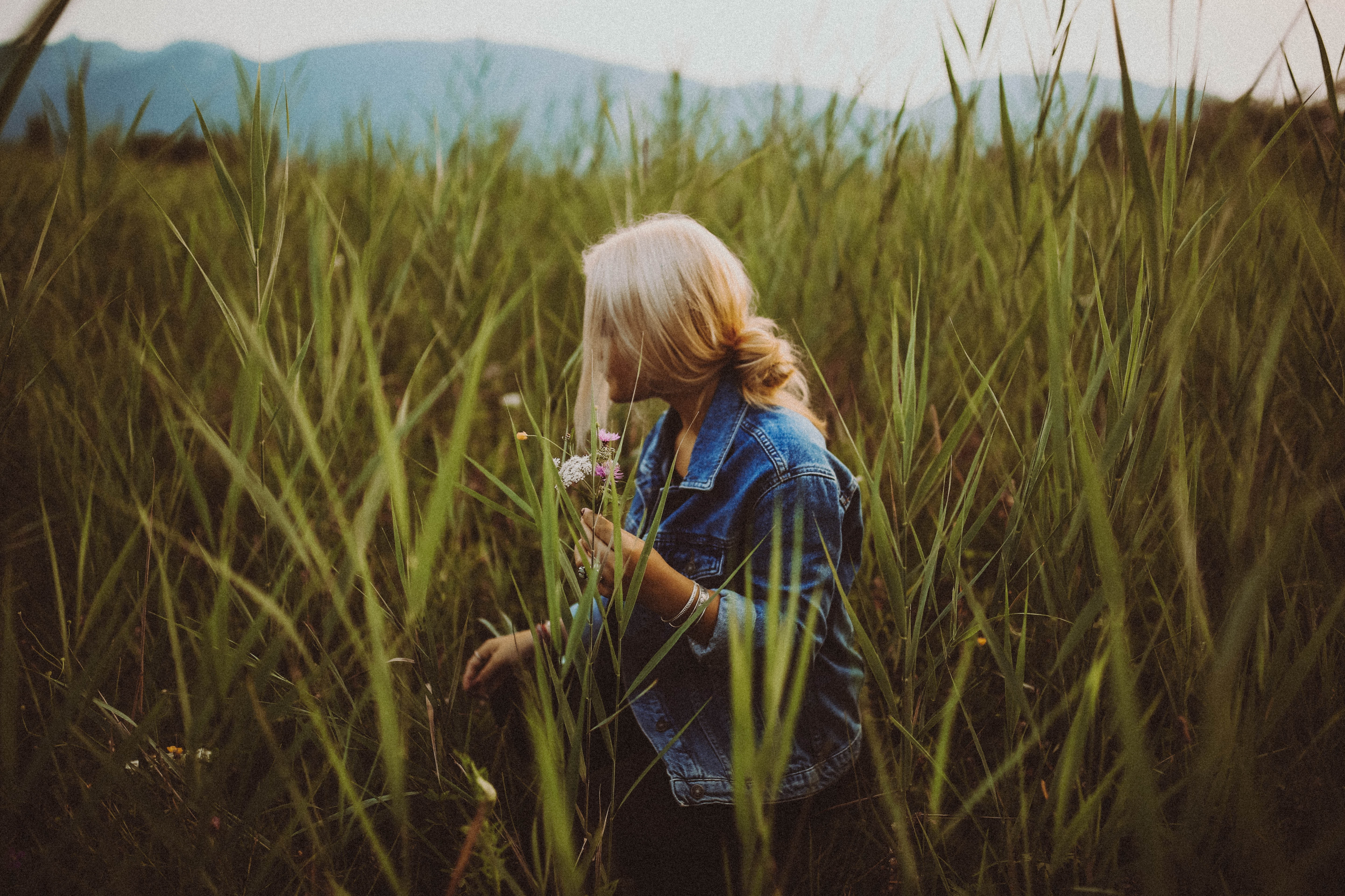 Woman walks alone through field of tall grass with wildflowers