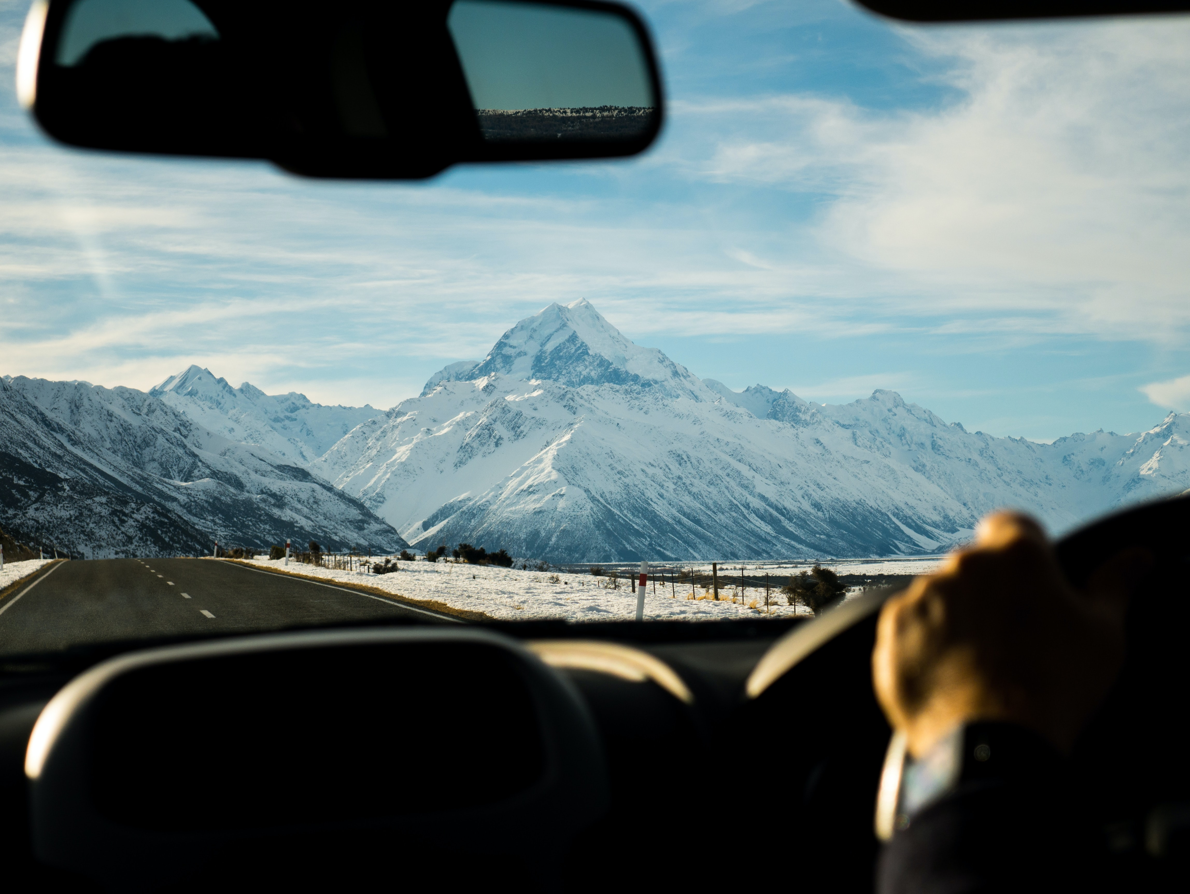 man driving towards mountain coated with snow