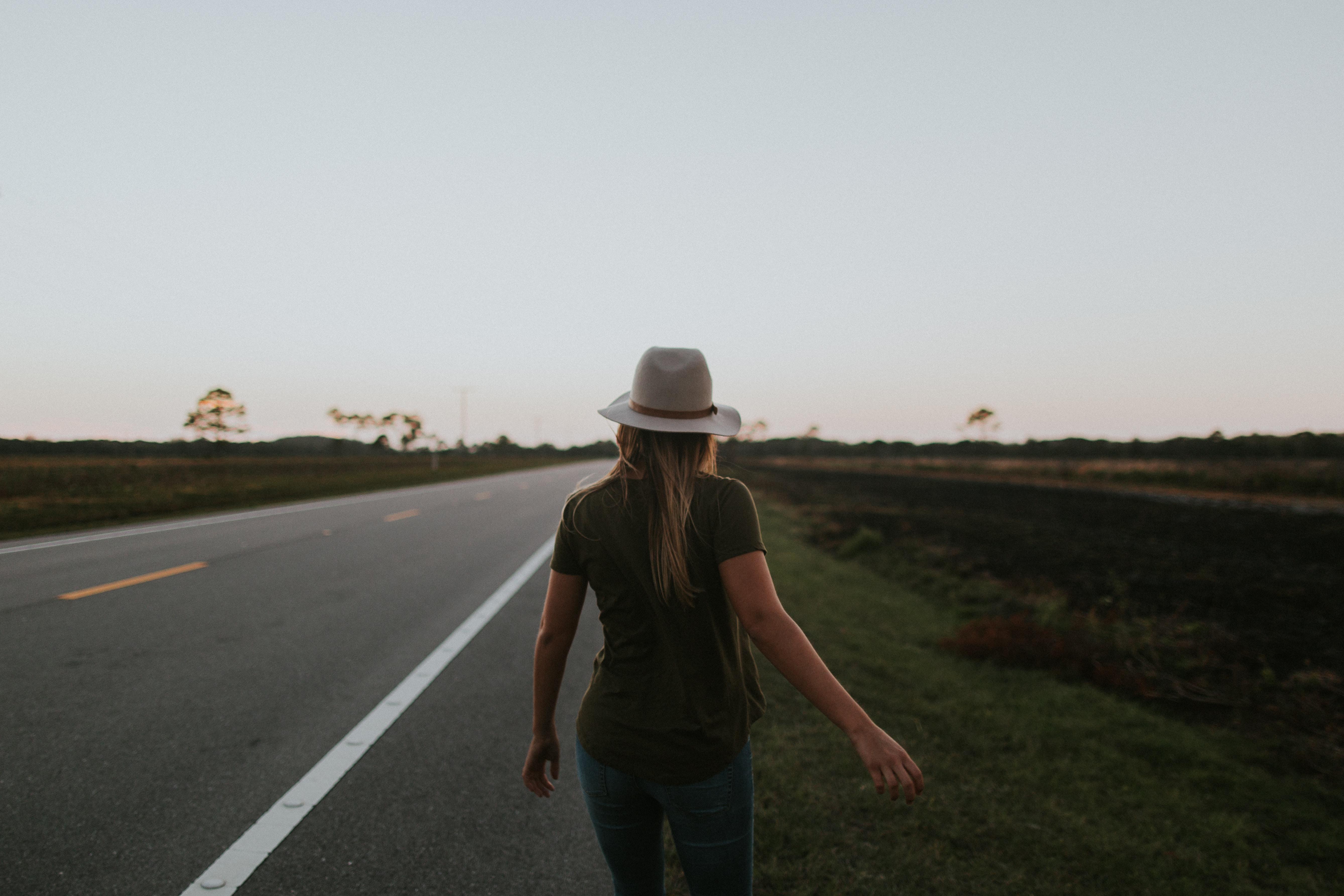 A woman wearing a hat walks away along a highway in daytime sunlight