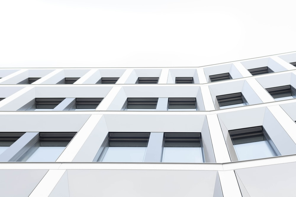 worm's eyeview photo of white concrete 3-storey building