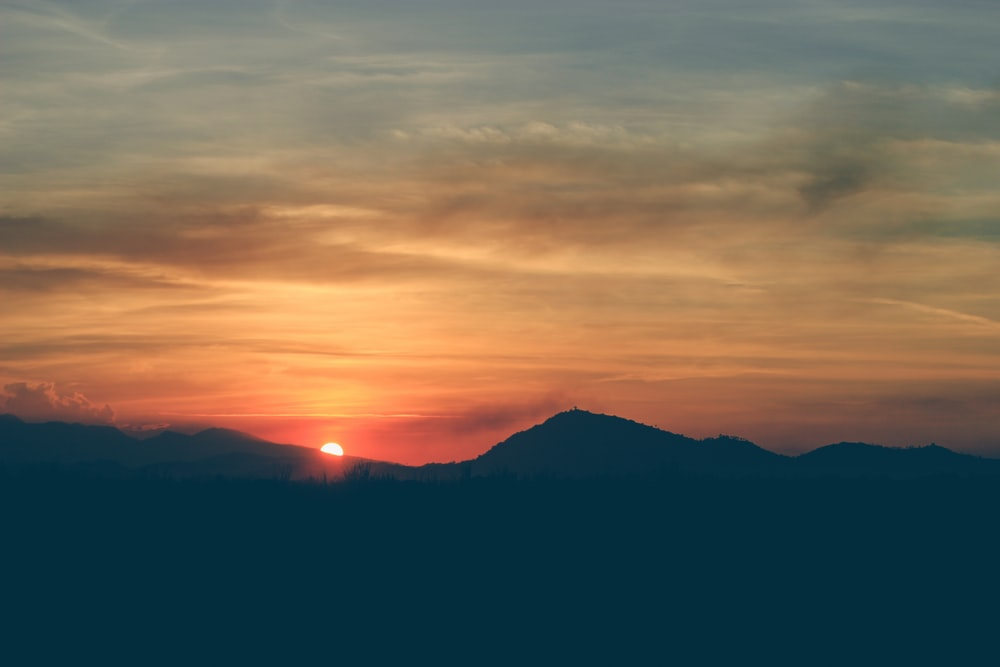 silhouette of mountains during golden hour photography