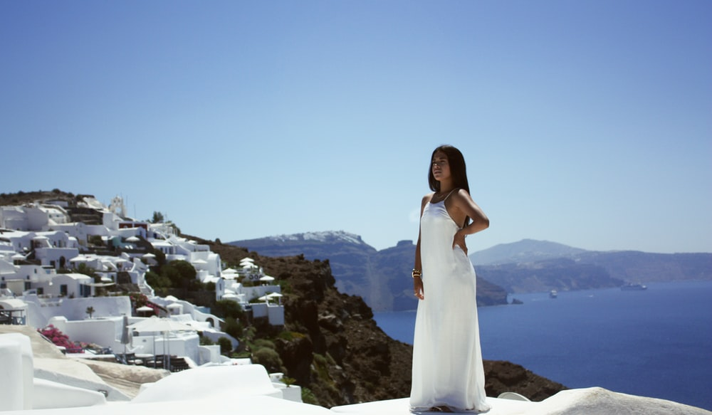 woman wearing white dress in front building beside sea