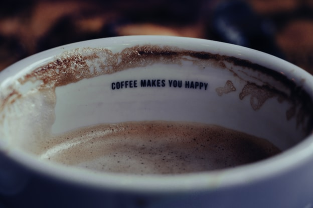 """The inside of a coffee cup reads: """"coffee makes you happy"""""""