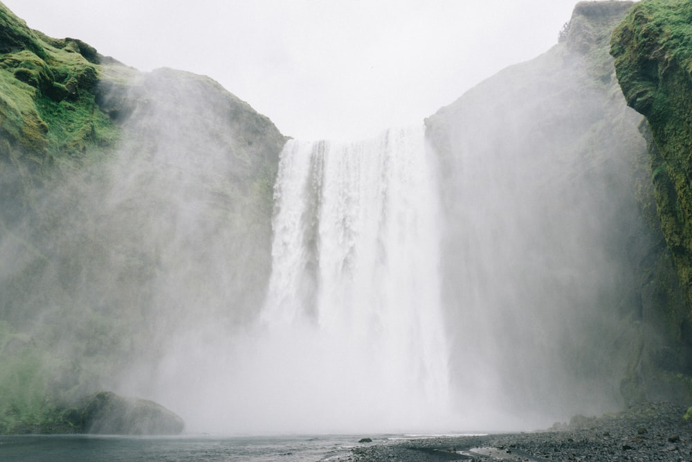 waterfall under cloudy sky