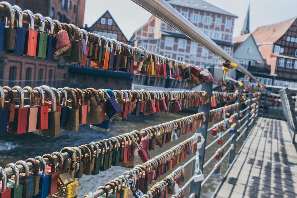 assorted-color padlock lot on balustrade beside canal