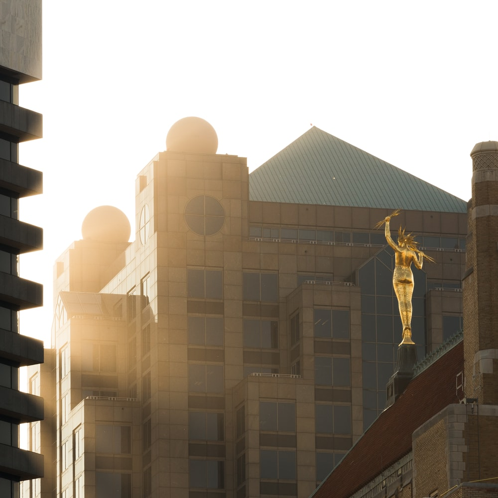 gold statue near brown concrete building during daytime