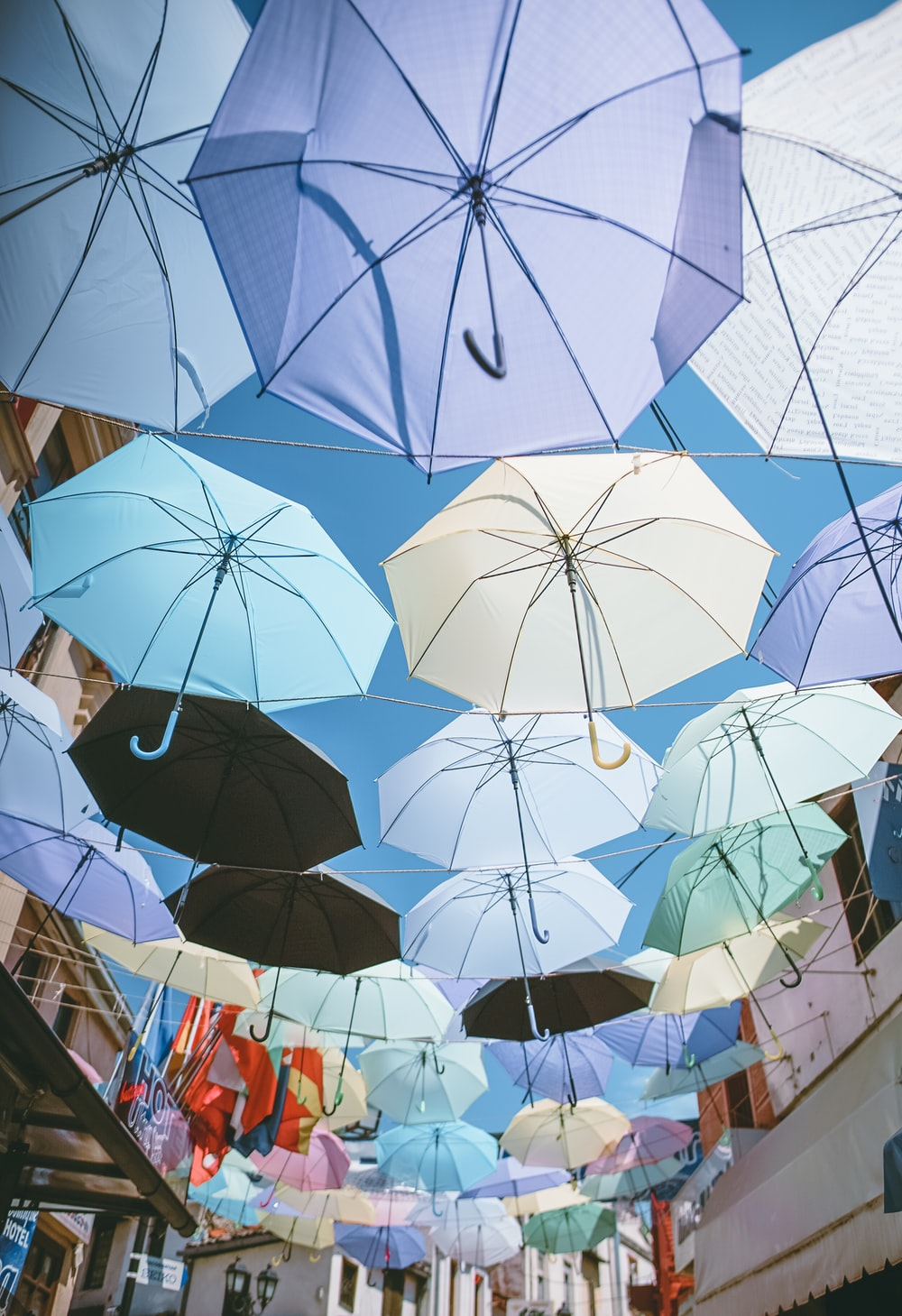 assorted-color umbrellas hanged on wires under blue sky during daytime