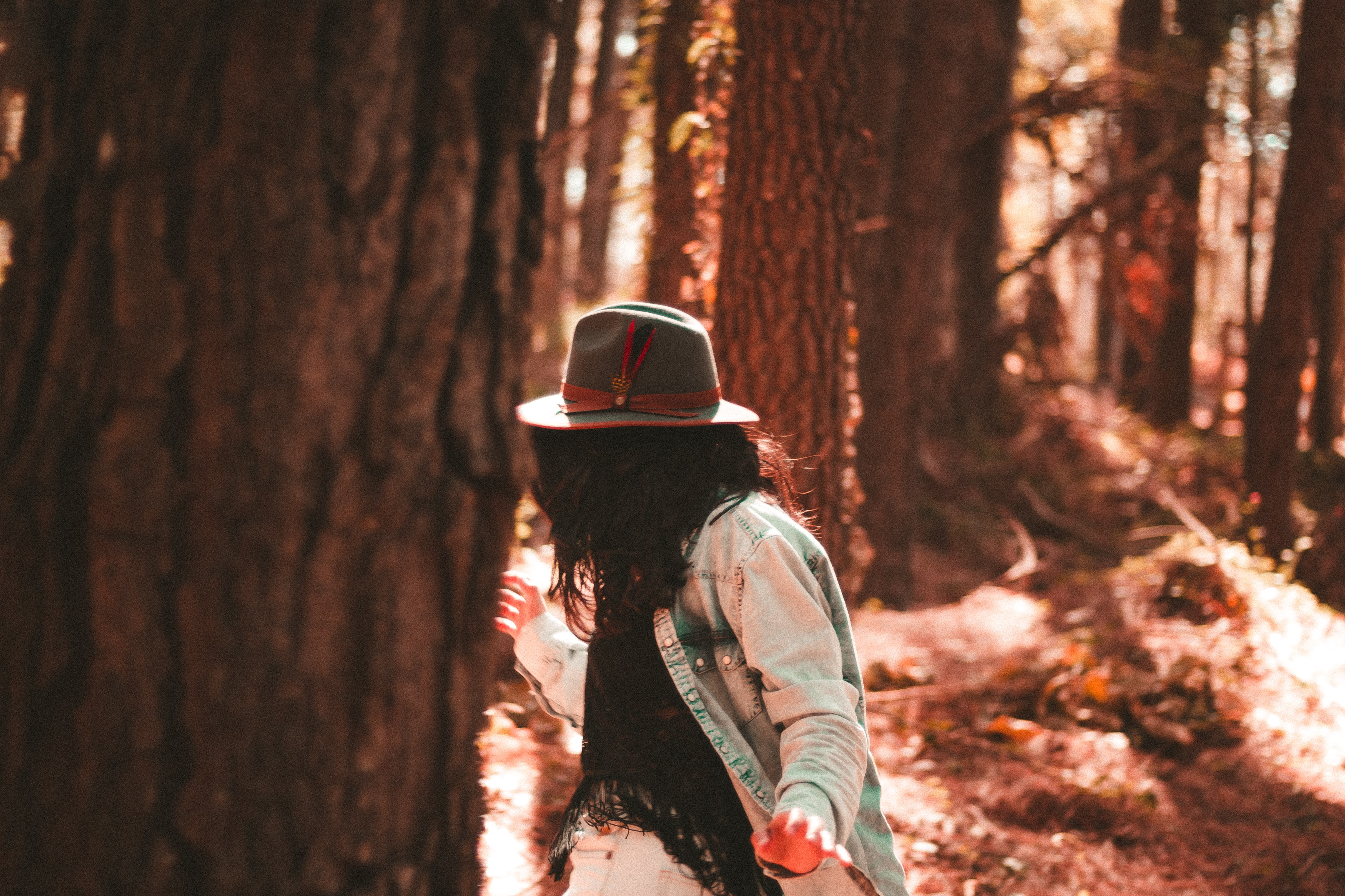 A woman wearing a hat with a feather in it and a denim shirt dancing in the forest
