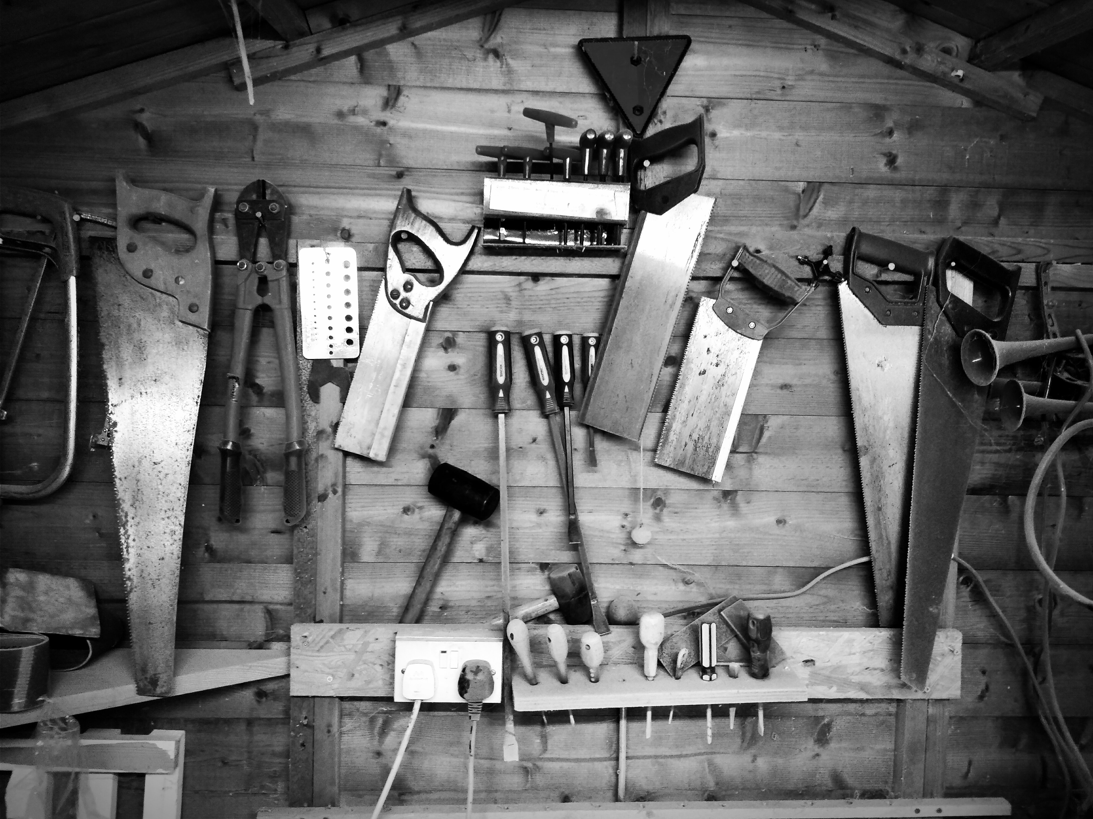 Black and white shot of assorted woodwork equipment on wooden wall, Broadstairs, Ramsgate, England, United Kingdom
