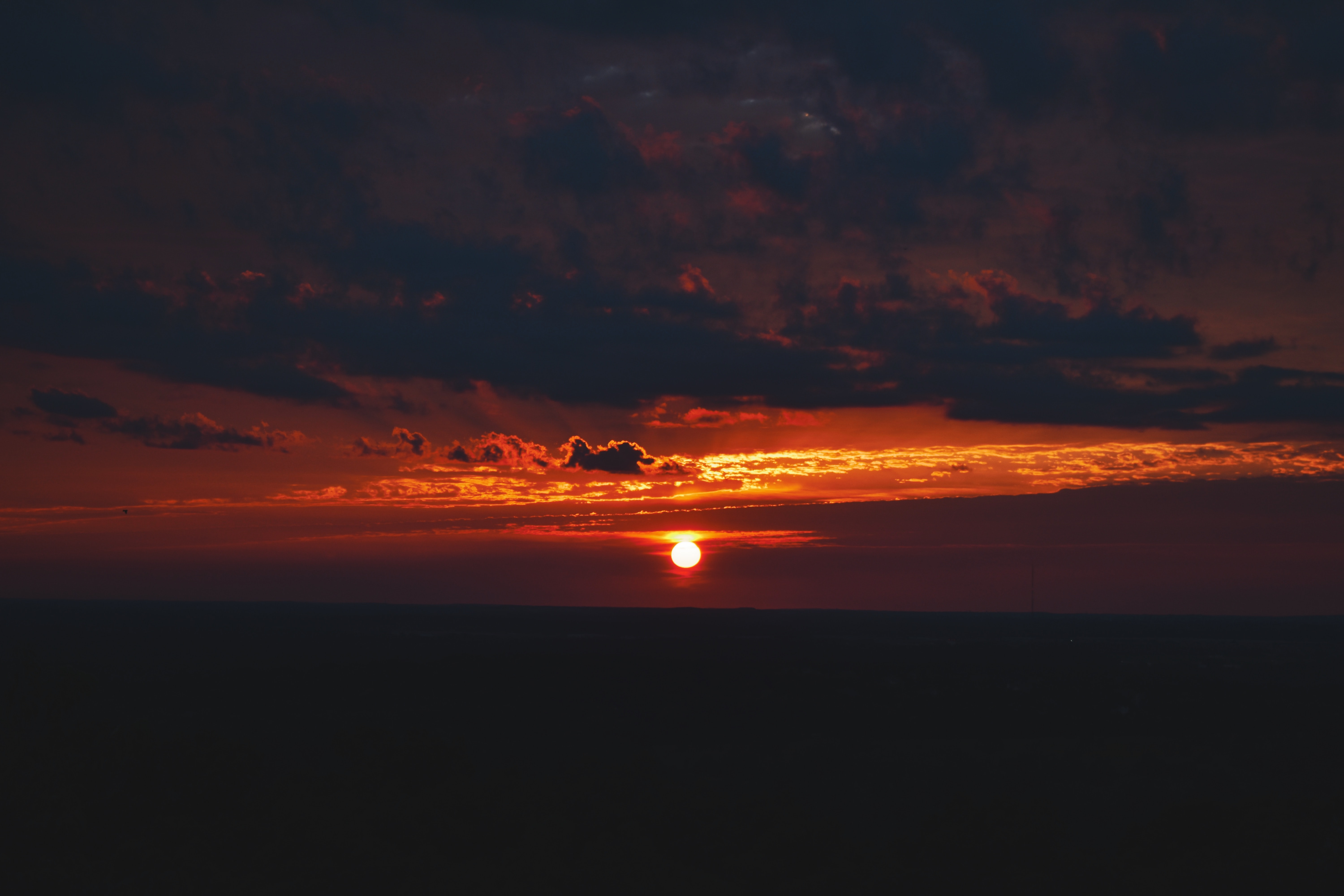 Red setting sun and clouds over a flat horizon