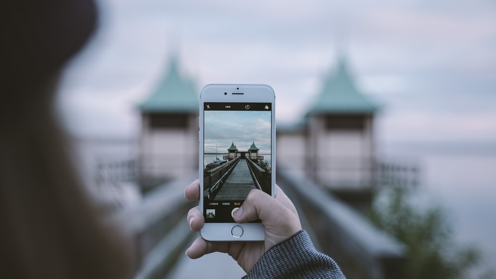 Woman taking picture of interesting architecture on iPhone with out of focus background, Persborg