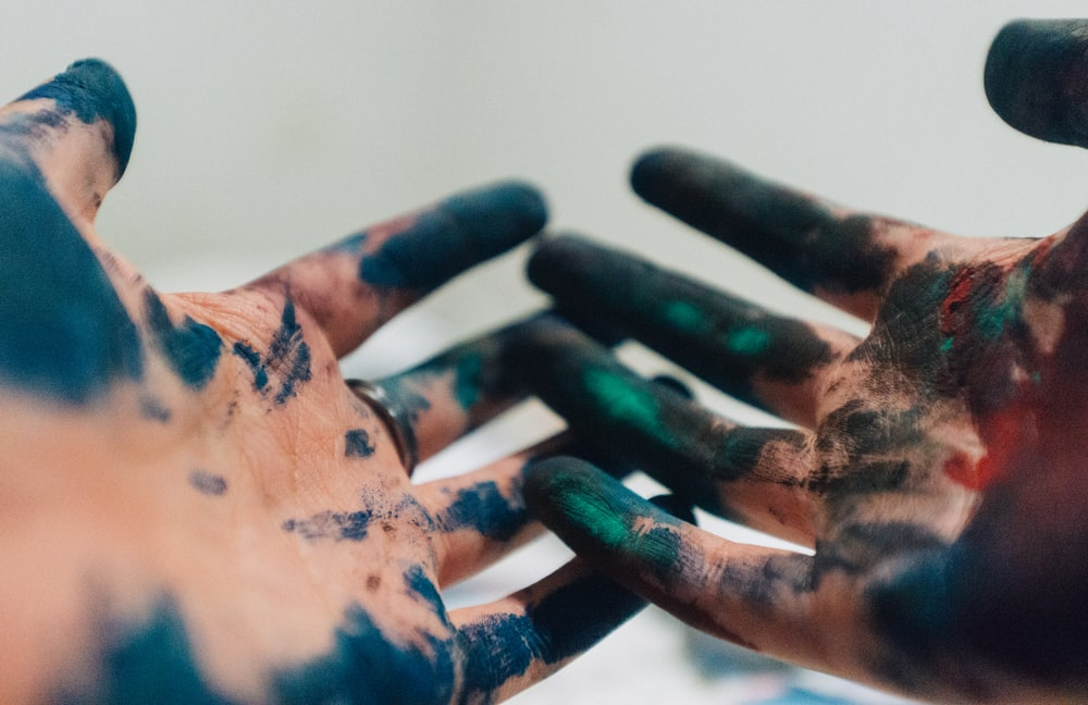 person hand with green and blue paint