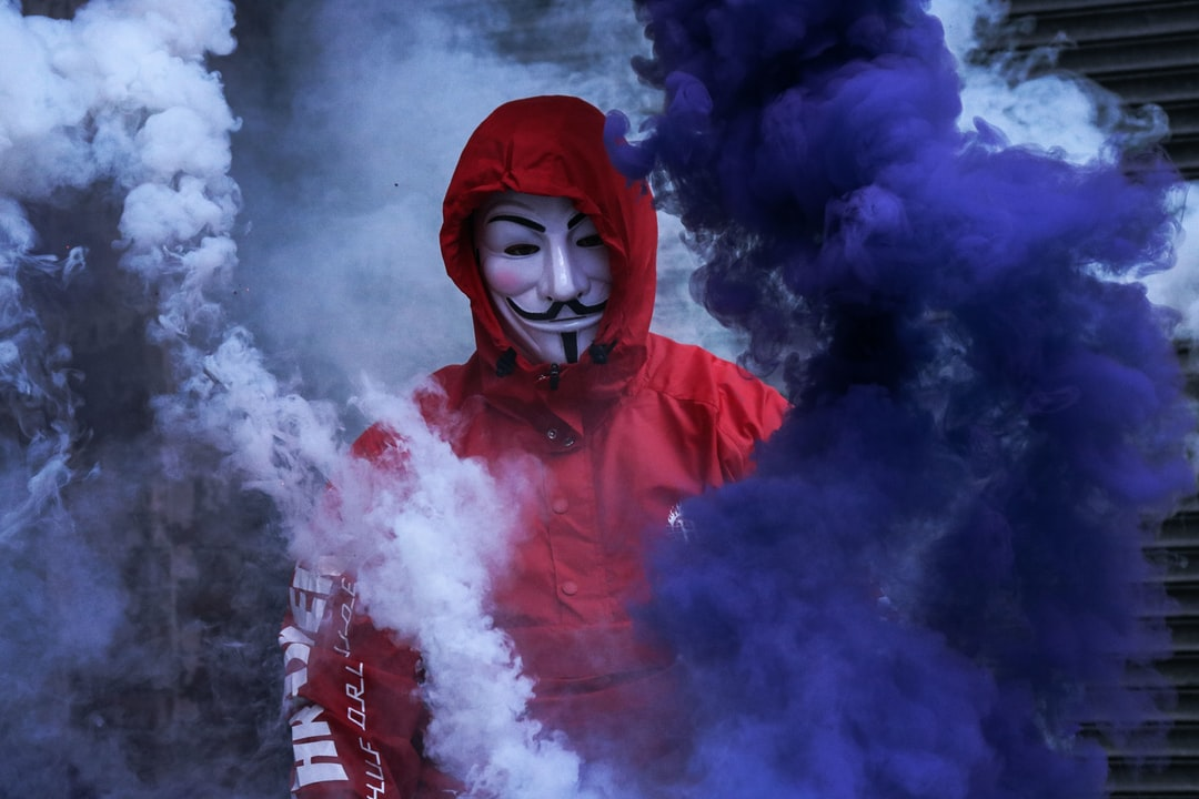man wearing red jacket surrounded by purple and white smoke