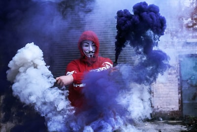 man wearing red hoodie standing near gray wall during daytime photo smoke grenade teams background