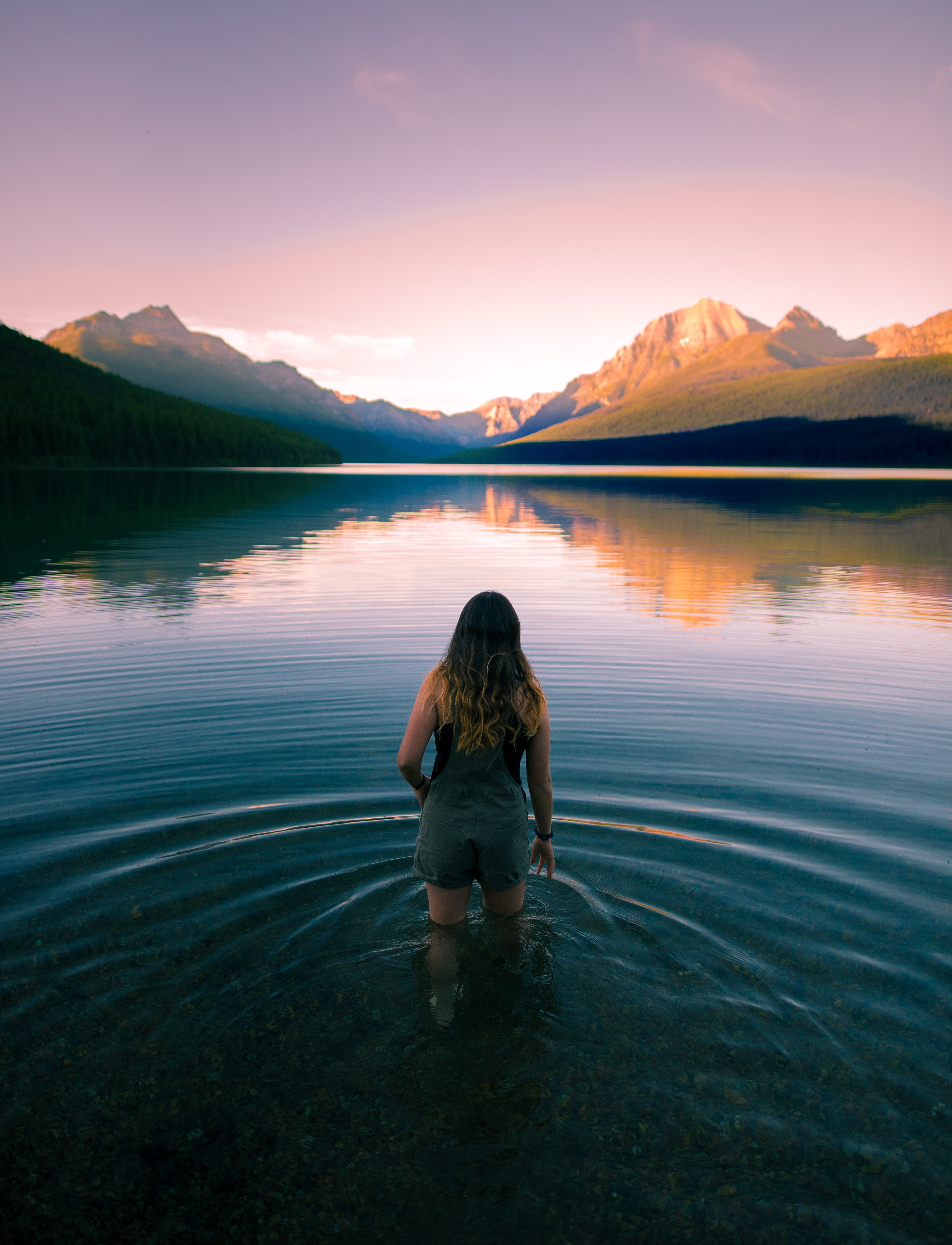 A girl wearing overall shorts standing in Bowman Lake during golden hour with the mountains in the background