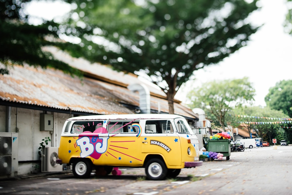 yellow and white Volkswagen Kombi parked near white building