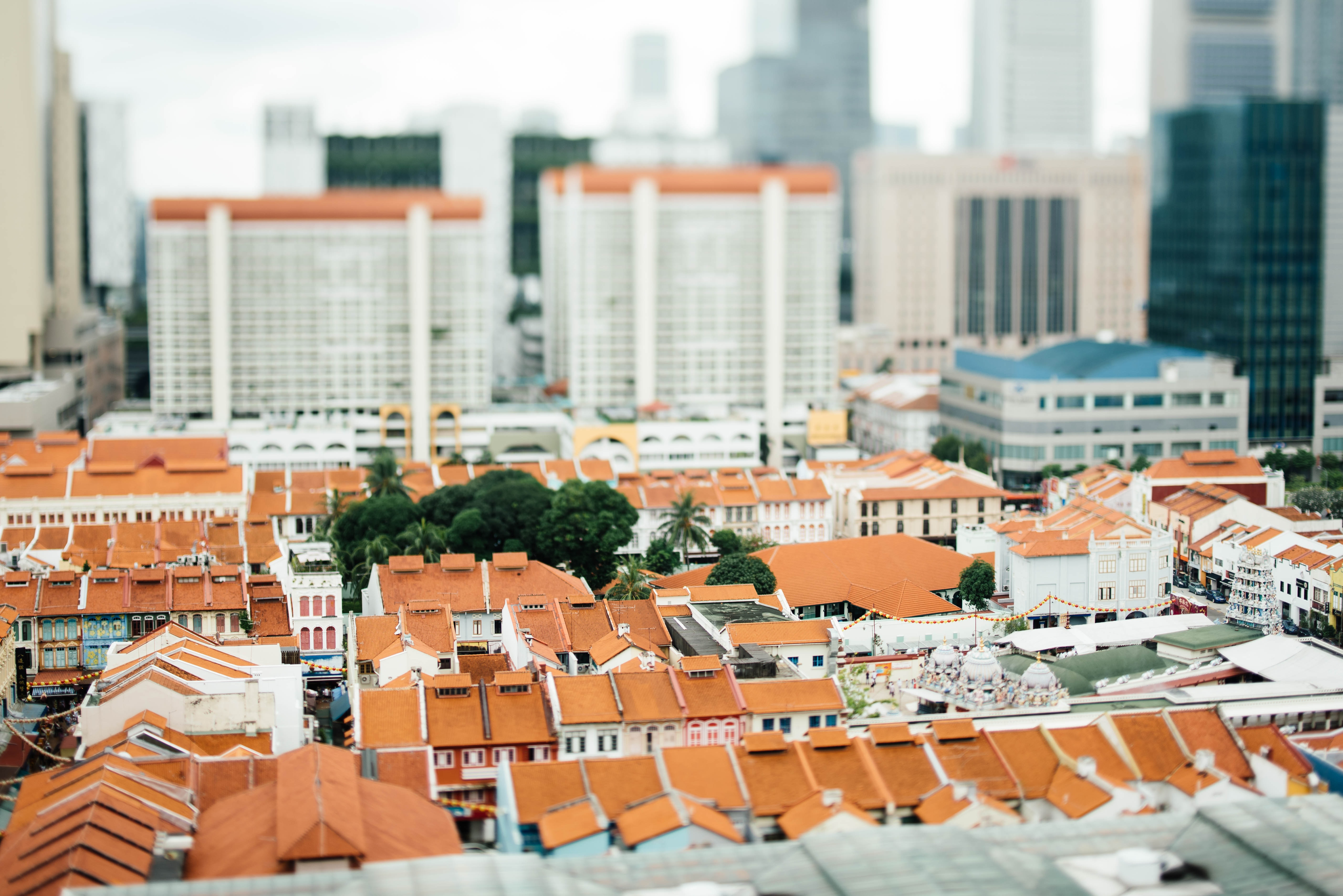 tilt-shift photography of white-and-orange houses surrounded by high rise buildings at daytime