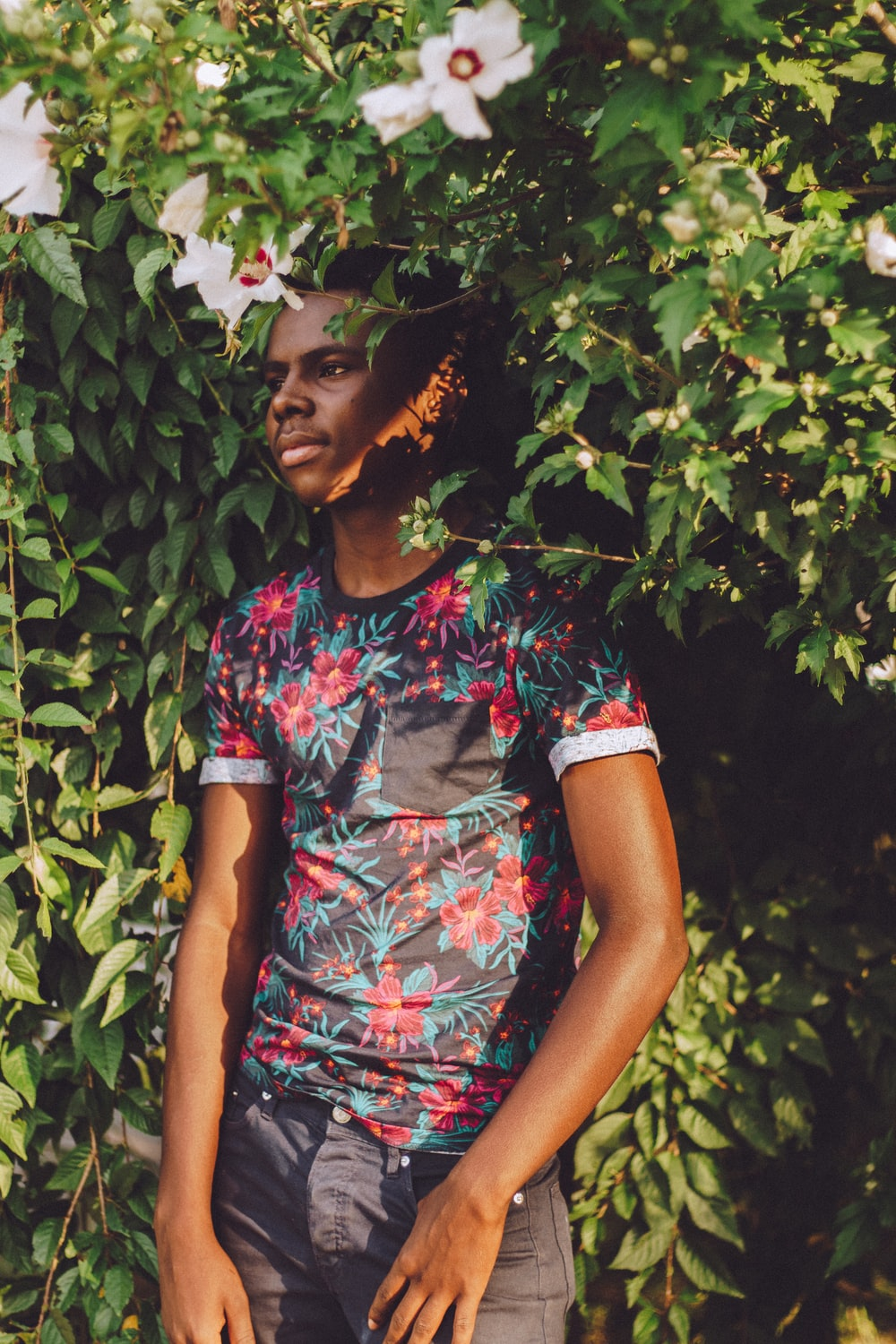 man wearing black, teal, and red floral t-shirt leaning green leaf plant with white flowers