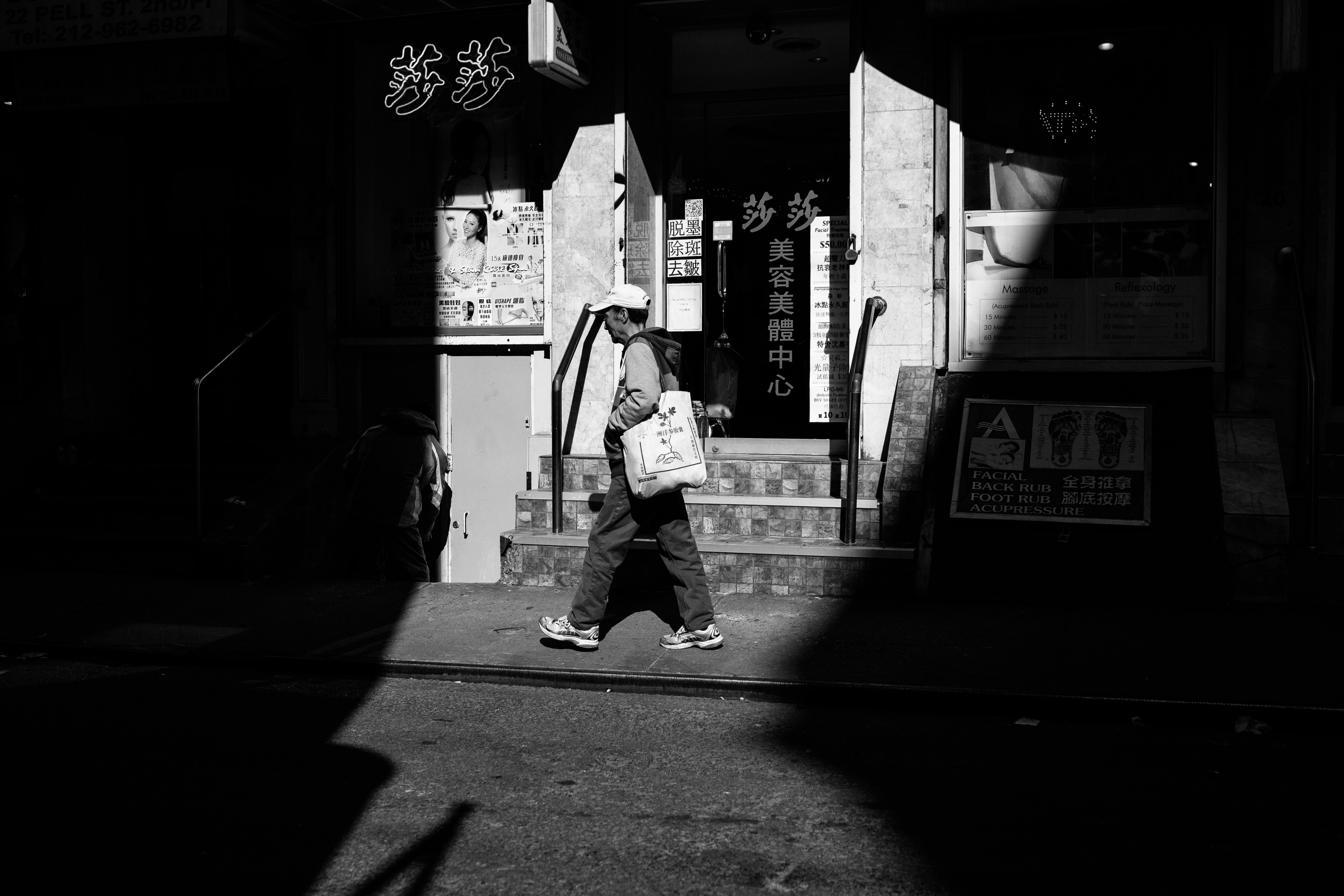 grayscale photography of person walking beside building