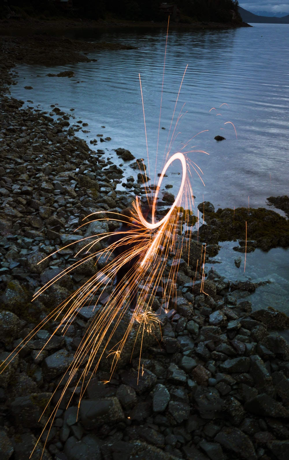 person standing on rock formation near body of water on steel wool photography